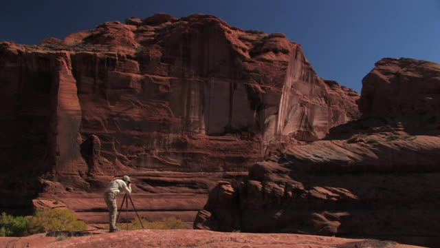 ws man taking photograph with camera on tripod/ canyon de chelly national monument, arizona - canyon de chelly stock videos & royalty-free footage
