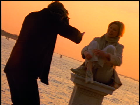 man taking photographs of woman sitting + posing on pedastal near water at sunset / venice, italy - 1999年点の映像素材/bロール