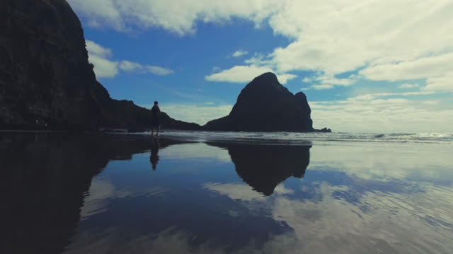 Man taking Photos at Piha Beach, Auckland, New Zealand.
