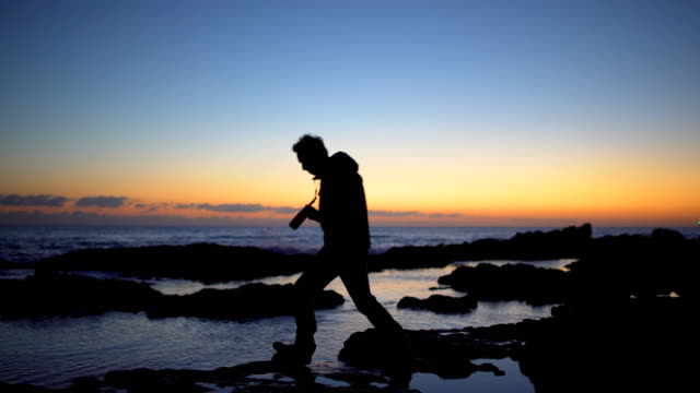 man taking photos in the coast at sunset - tide pool stock videos & royalty-free footage