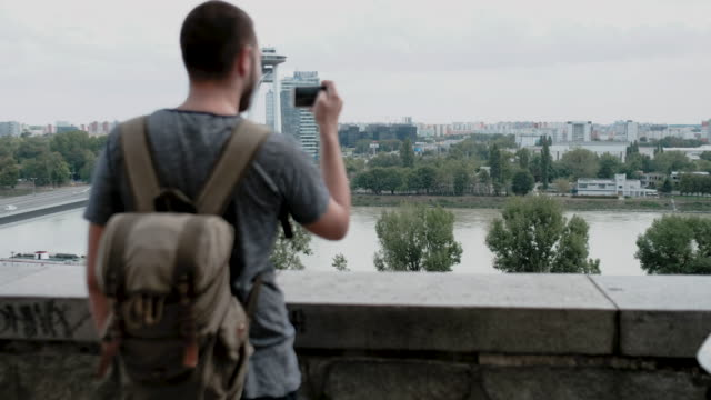Man taking photos of city on his smart phone