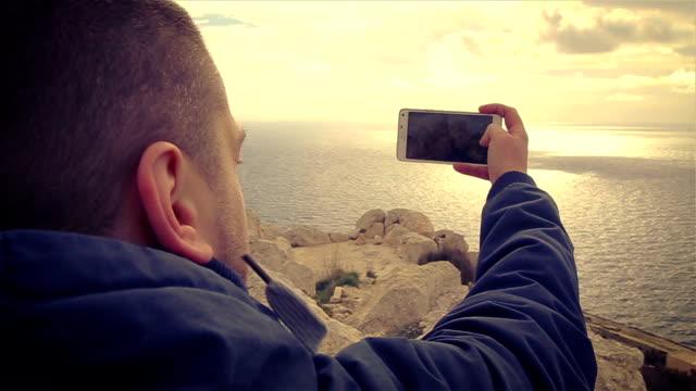 vídeos y material grabado en eventos de stock de hombre tomando fotos de olas en un acantilado por smartphone, puesta de sol - acantilado
