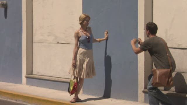 ws pan man taking photos of woman along street / merida, mexico  - handbag stock videos and b-roll footage