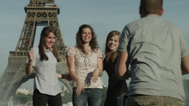 ms man taking photos of young women in front of eiffel tower / paris, france - eiffel tower paris stock videos & royalty-free footage
