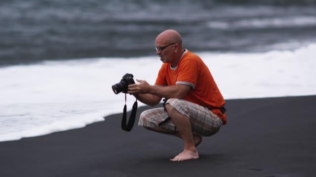 man taking photos on the beach