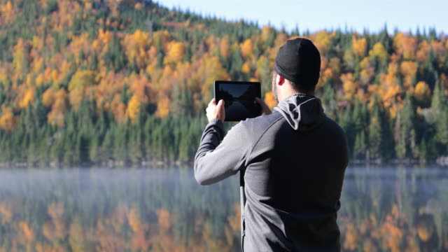 man taking picture of lake nature with digital tablet - photographing stock videos & royalty-free footage