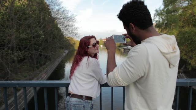vidéos et rushes de man taking picture of woman looking out over river on bridge leaning on railing, selfie, kissing - embrasser sur la bouche