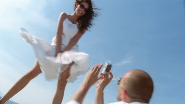 vídeos y material grabado en eventos de stock de man taking pictures of woman standing on ledge on windy day / capri - falda