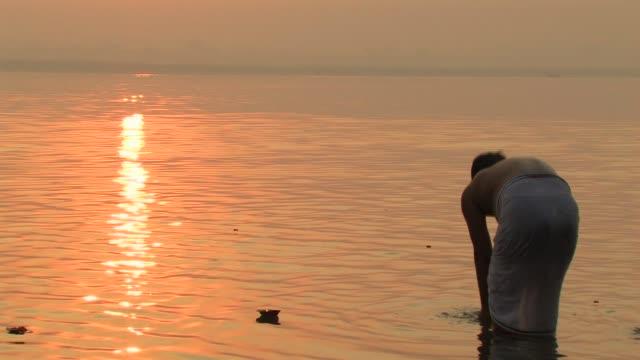 ms, man taking ritual bath, hindu votive candle (diya) floating on ganges river, sunrise, rear view, varanasi, uttar pradesh, india - ceremony stock videos & royalty-free footage