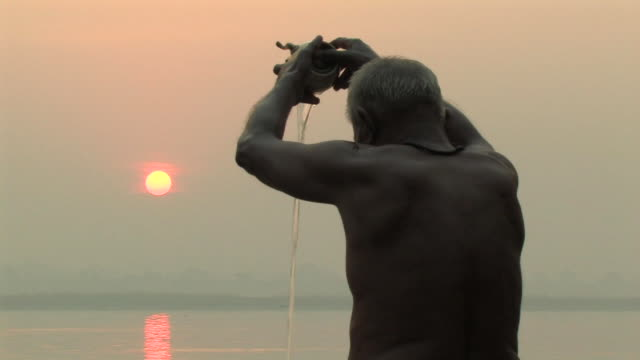 CU, Man taking ritual bath in Ganges river at sunrise, rear view, Varanasi, Uttar Pradesh, India