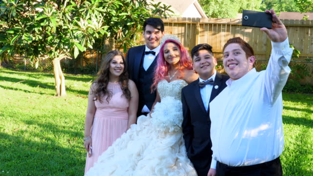 ms man taking selfie of family standing with young woman in quinceanera gown in backyard - 14 15 anni video stock e b–roll
