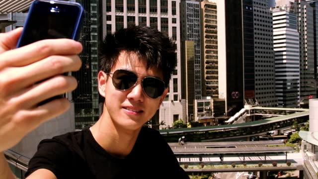 man taking selfie with mobile phone - männlicher teenager allein stock-videos und b-roll-filmmaterial