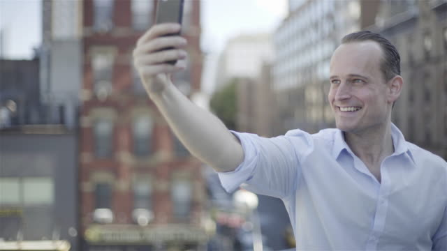 man taking selfie with smart phone - hochgekrempelte ärmel stock-videos und b-roll-filmmaterial