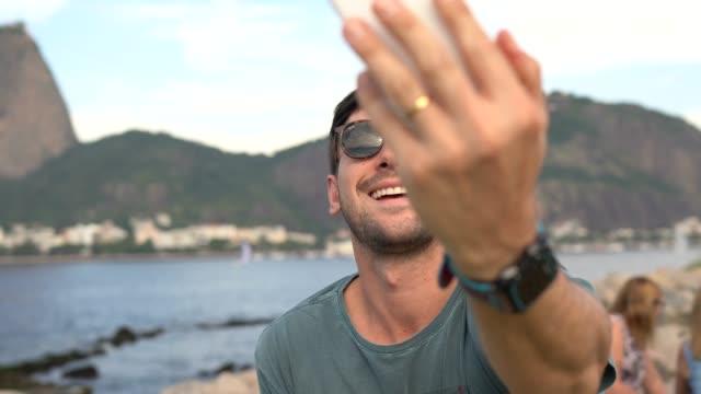 man taking selfies of mountains in rio de janeiro - rio de janeiro stock videos & royalty-free footage