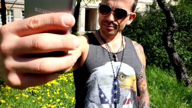 stockvideo's en b-roll-footage met man nemen van selfies met zijn mobiele telefoon buiten - sunny