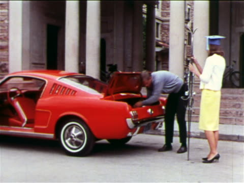 1965 man taking skis from woman in graduation cap to put them in trunk of ford mustang / industrial - ford mustang stock videos and b-roll footage