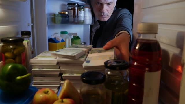 pov man taking stacks of euros out of a fridge - ebenezer scrooge stock videos & royalty-free footage