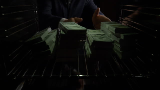 pov man taking stacks of u.s. dollars out of oven - greed stock videos and b-roll footage