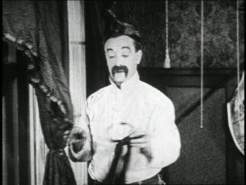 b/w 1923 man (snub pollard) taking tie attached to rigid band on curtain + putting it on / short - 1923 stock videos & royalty-free footage