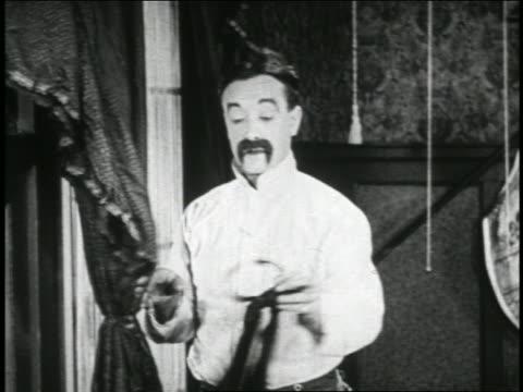 b/w 1923 man (snub pollard) taking tie attached to rigid band on curtain + putting it on / short - 1923 bildbanksvideor och videomaterial från bakom kulisserna