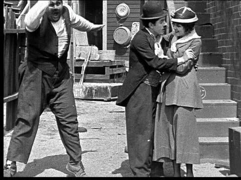 1918 b/w man taking to woman in alley/ other man angrily running in to start fight - oliver hardy stock videos & royalty-free footage