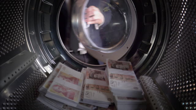 pov man taking uk pounds out of a washing machine - criminal stock videos and b-roll footage