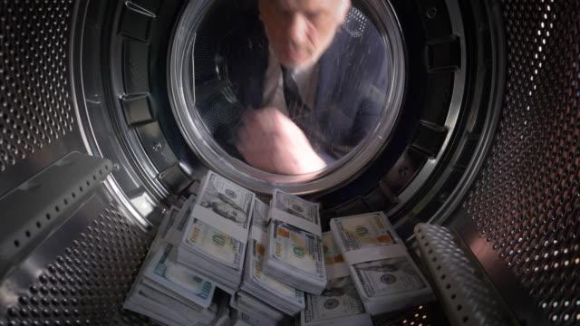 vidéos et rushes de pov homme prenant dollars américains sur une machine à laver - avidité