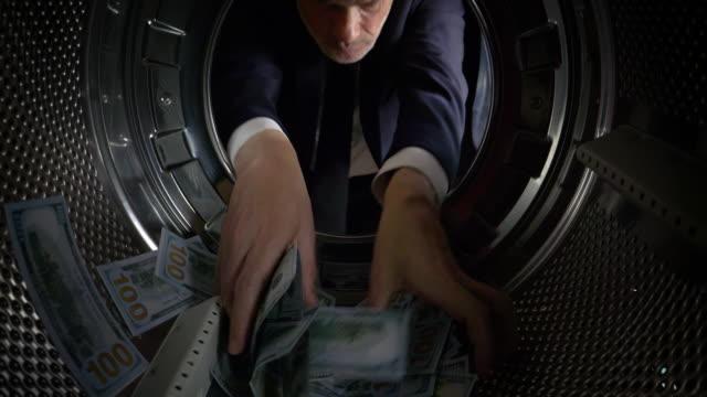 pov man taking us dollars out of a washing machine - ebenezer scrooge stock videos & royalty-free footage