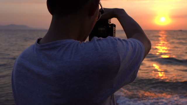 cu man taking video and photo of sunset or sunrise at the beach - filming stock videos & royalty-free footage