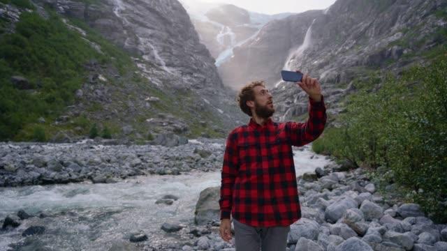 ノルウェーの氷河の近くでスマートフォンでビデオを撮っている男 - 風致地区点の映像素材/bロール