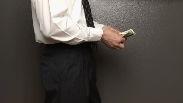 MS, Man taking wad of American dollars from pocket, mid section