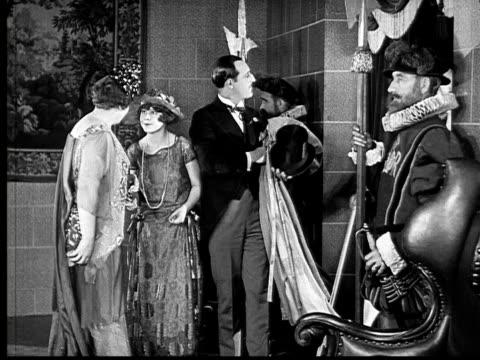 vidéos et rushes de 1924 b&w ms man taking women's coats and ushering women past guards and into royal palace  - 1924