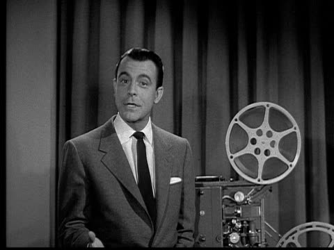 vídeos de stock e filmes b-roll de ms, b&w, man talking and turning on film projector, 1940's  - fato completo