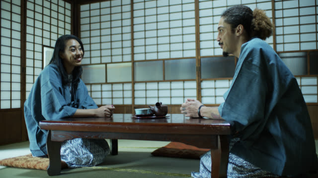 vídeos de stock, filmes e b-roll de homem que fala animadamente à amiga no ryokan em japão - washitsu