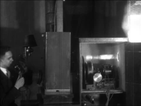 b/w 1927 pan man talking into telephone + beam of light going thru boxes - experimental television - 1920 stock-videos und b-roll-filmmaterial
