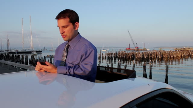 ms man talking on bluetooth and typing on mobile phone while standing in sunroof opening of car / portland, me, united states - sun roof stock videos & royalty-free footage