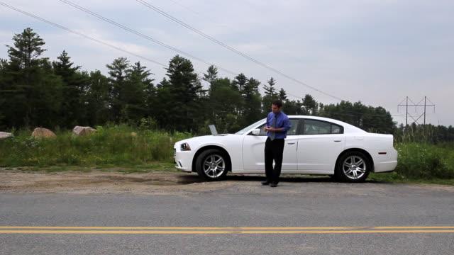 ws man talking on bluetooth beside car / portland, me, united states - シャツとネクタイ点の映像素材/bロール
