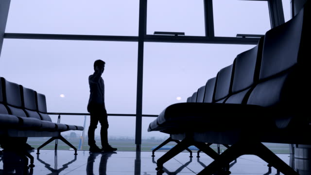 Man praten op mobiele telefoon bij luchthaven gate