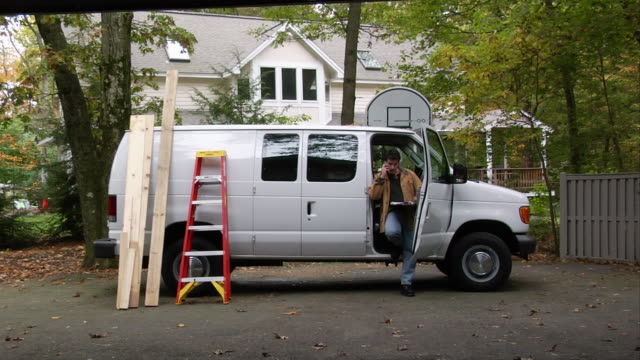 man talking on cell phone in front passenger doorway of van with ladder and wood planks leaning against it / getting off phone and opening side doors of van - 電話を切る点の映像素材/bロール