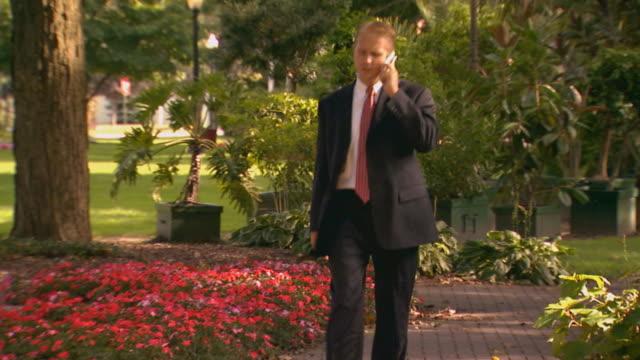 vídeos de stock e filmes b-roll de man talking on cell phone in park - fato completo