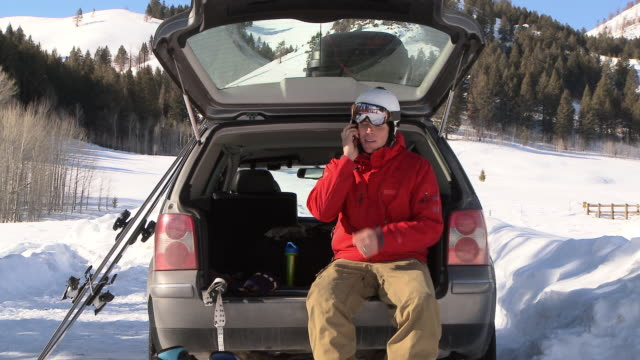 man talking on cell phone sitting at back of car in winter clothing and ski gear / ketchum, idaho, united states - ski clothing stock videos and b-roll footage