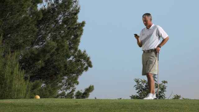 ws man talking on cell phone standing on golf course / palma de mallorca, mallorca, baleares, spain - links golf stock videos & royalty-free footage