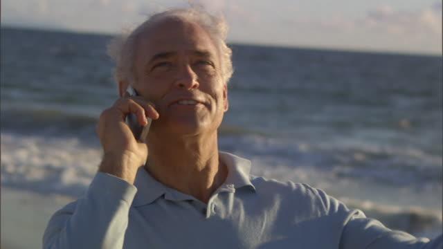 slo mo cu man talking on cell phone with sea in background / vista del mar, california, usa - mar bildbanksvideor och videomaterial från bakom kulisserna
