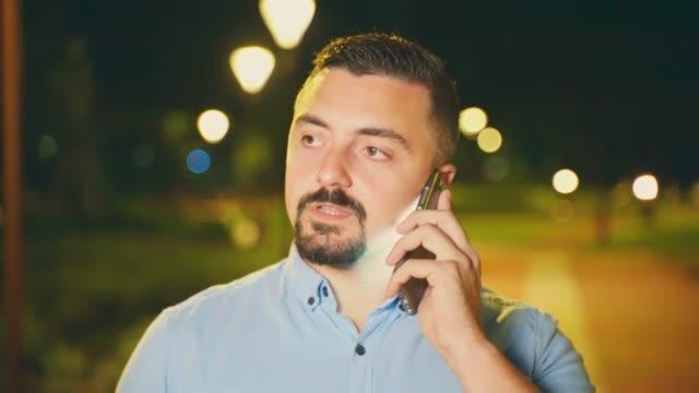 Man talking on his smart phone outdoors at night close up