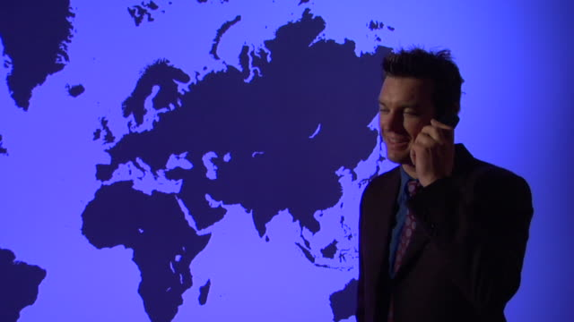 MS, PAN, Man talking on mobile phone against blue World map showing Europe and Americas