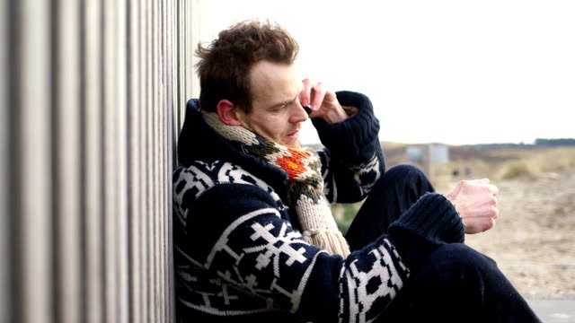 MS Uomo parla al cellulare in spiaggia