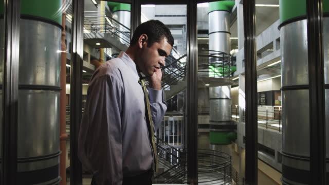 MS POV Man talking on mobile phone in modern elevator in office building / Orem, Utah, USA