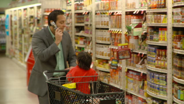 ms pan selective focus man talking on mobile phone shopping with son (2-3) at supermarket, richmond,  virginia, usa - shopping trolley stock videos and b-roll footage