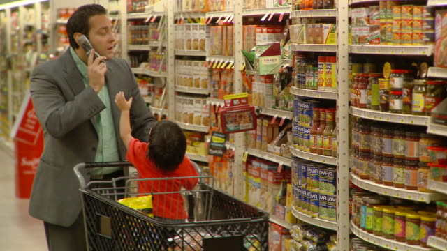 MS PAN Man talking on mobile phone shopping with son (2-3) at supermarket, Richmond,  Virginia, USA