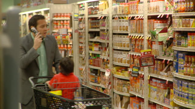 vidéos et rushes de ms pan man talking on mobile phone shopping with son (2-3) at supermarket, richmond,  virginia, usa - caddie